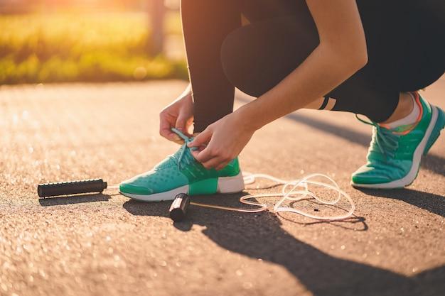 Спортсменка завязывает шнурки на кроссовках и готовится делать кардио упражнения со скакалкой на улице