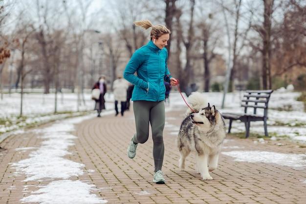 Спортсменка бегает вместе со своей собакой в парке в снежную погоду. зимний фитнес, домашние животные, дружба