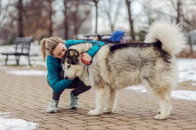 雪の降る天気で公園でしゃがみながら犬にキスをし、抱きしめるスポーツウーマン。ペット、レクリエーション、週末のアクティビティ