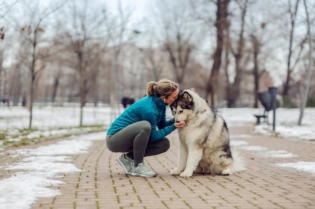 스포츠우먼은 눈 덮인 날씨에 공원에서 웅크리고 있는 동안 개를 껴안고 키스합니다. 애완 동물, 레크리에이션, 주말 활동