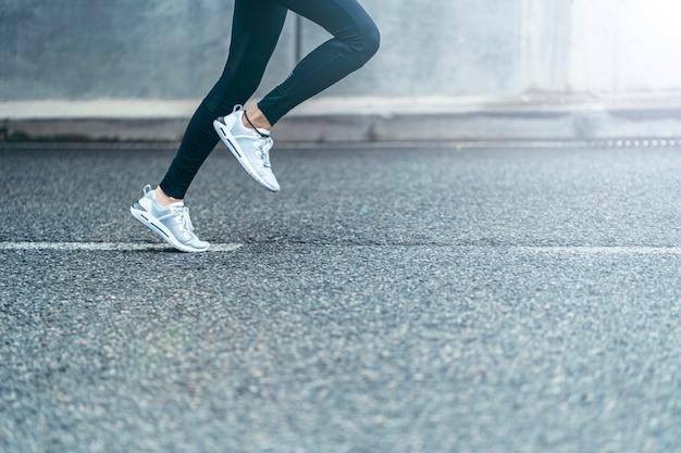 Ноги спортсменки бегут по дороге