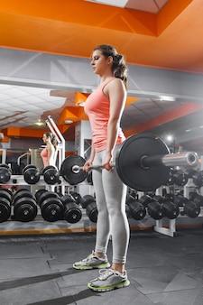 Спортсменка, поднимающая тяжелую штангу в тренажерном зале