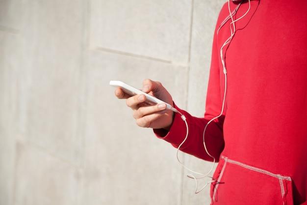 Спортсменка слушает музыку с помощью смартфона