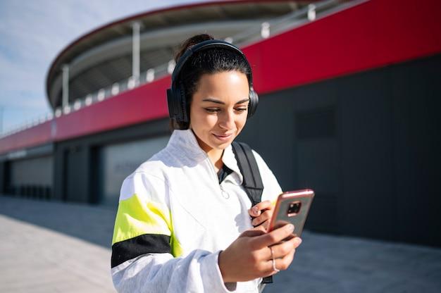通りを歩いてヘッドフォンで音楽を聴くスポーツ選手