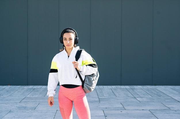 路上でヘッドフォンで音楽を聴くスポーツ選手