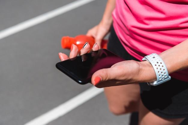Спортсменка смотрит на смартфон во время пробежки по беговой дорожке