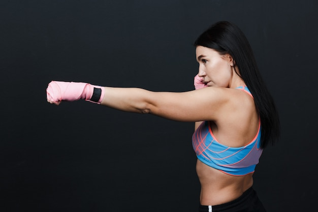 Sportswoman muay thai strong woman boxer posing in training studio at black background