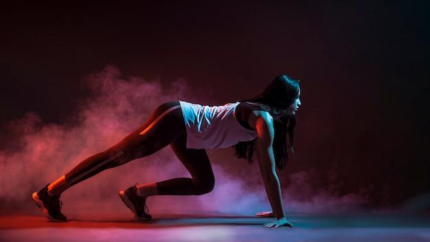 Спортсменка на корточках начинает в темноте