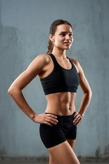 Sportswoman 회색 벽에 고립 된 스포츠에서 포즈