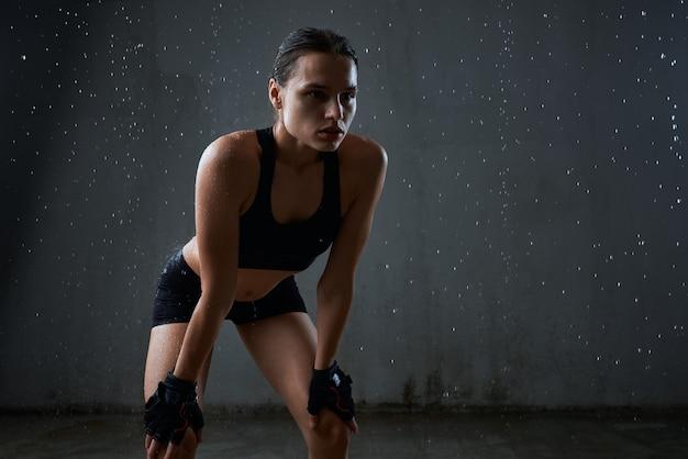 Sportiva che posa in abiti sportivi isolati su gray