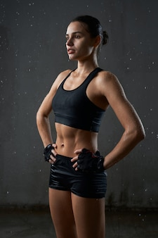 Sportswoman posing in sportswear isolated on gray
