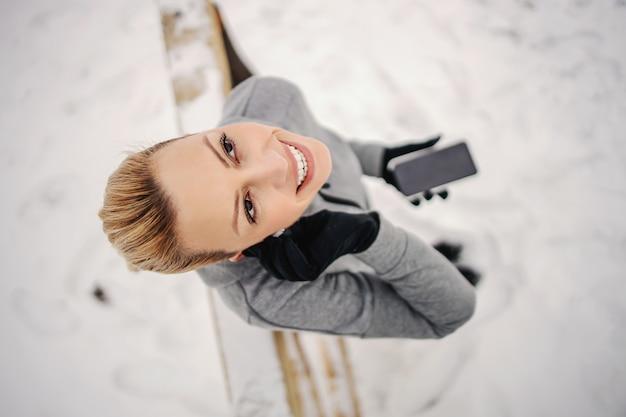 Спортсменка надевает наушники, стоя в снегу зимой. зимний фитнес, технологии, телекоммуникации