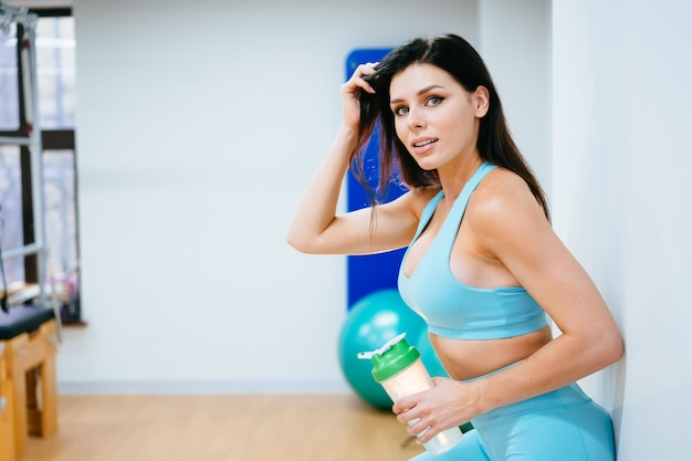 Sportswoman resting and drinking water on stairs in gym