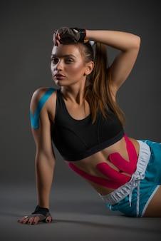 Спортсменка отдыхает с наклейками на животе и плечах