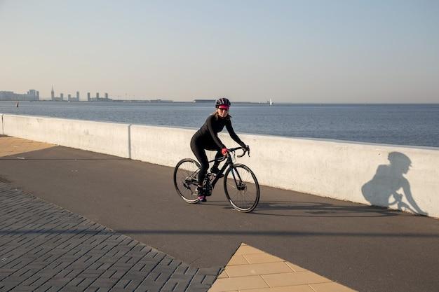 スポーツウーマンは湾の堤防に沿って自転車に乗る