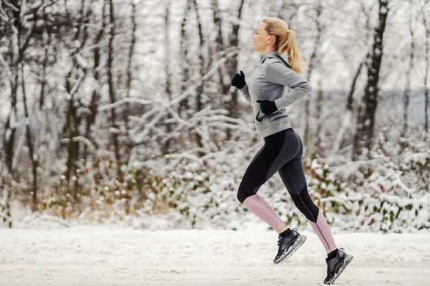 겨울에 자연 속에서 눈 덮인 흔적을 빠르게 달리는 스포츠 우먼.