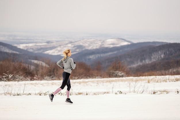 Спортсменка работает на природе по заснеженной дороге зимой. здоровый образ жизни, зимний фитнес, холода