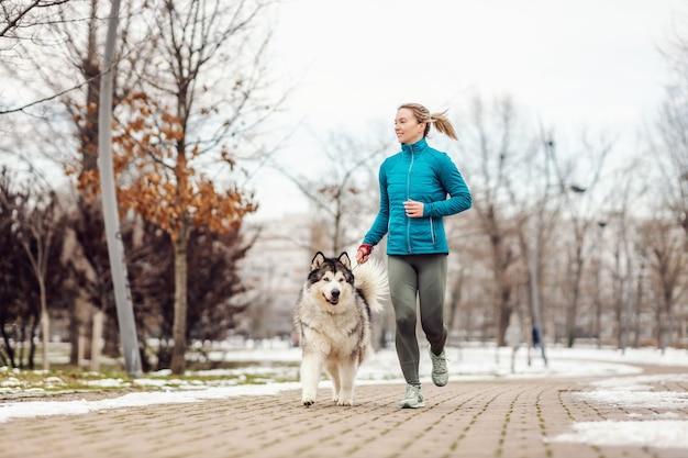 추운 겨울 날에 가죽 끈에 그녀의 강아지와 함께 공원에서 실행하는 sportswoman. 건강한 생활, 추운 날씨, 눈, 도시 생활