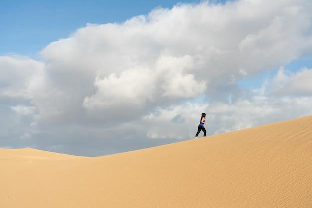 砂丘で走っているスポーツウーマン-セレクティブフォーカス
