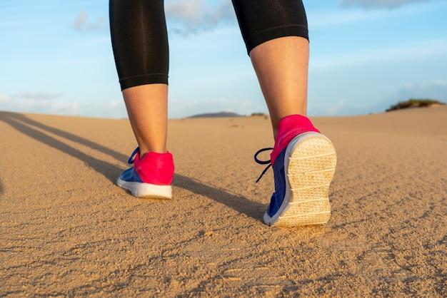 모래 언덕에서 달리는 스포츠우먼 - 선택적 초점