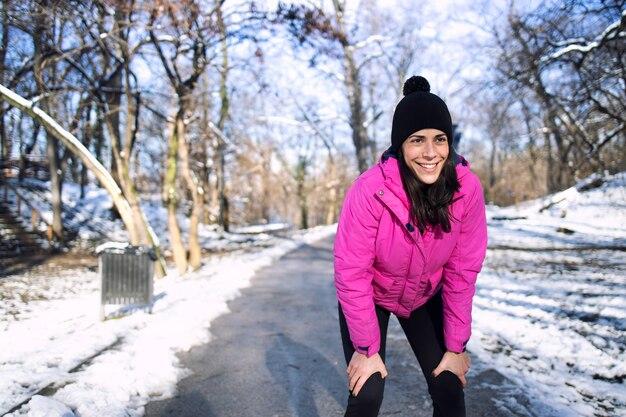 눈과 겨울 동안 공원에서 실행하는 sportswoman.