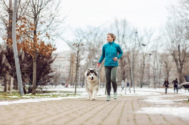 Спортсменка работает вместе со своей собакой в парке в снежную погоду. зимний фитнес, домашние животные, дружба