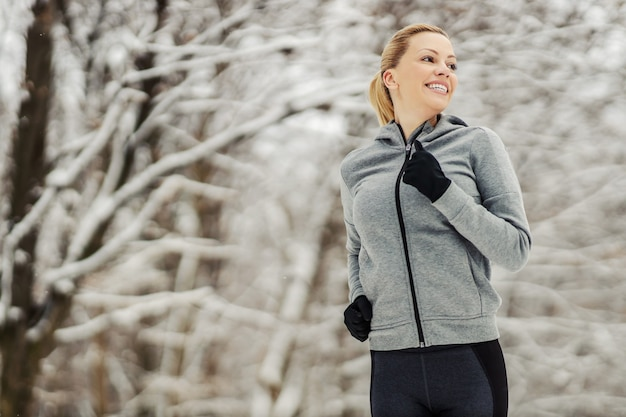 Sportswoman running in woods ar snowy winter day. winter fitness, healthy life, nature