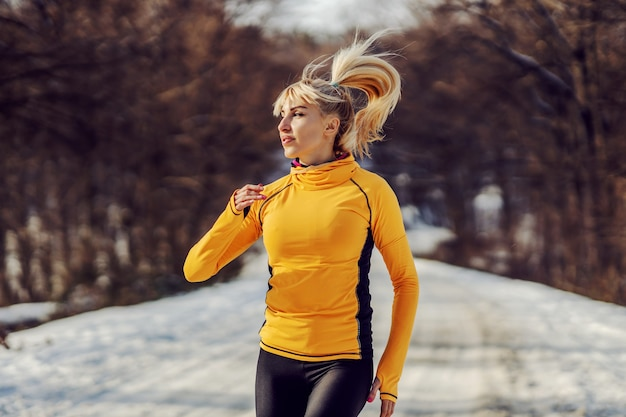 Sportswoman in shape running in forest at snowy winter day. winter fitness, cardio exercises, chilly weather