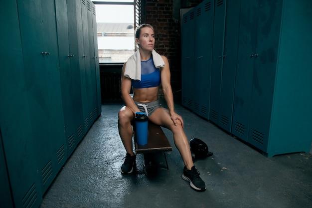 トレーニング後、スポーツウーマンは楽屋のベンチに座る