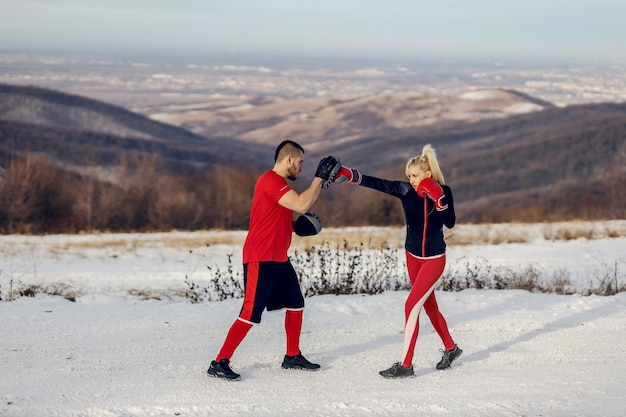雪の降る冬の日にコーチと自然の中でボクシンググローブでスパーリングをするスポーツウーマン。ボクシング、冬のフィットネス、アウトドアフィットネス