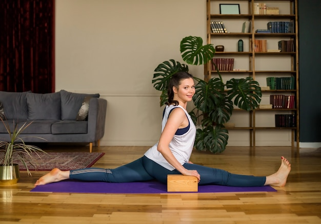 Sportswoman in a sports uniform performs splits with the help of bricks on the mat in the room