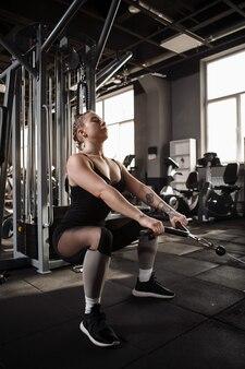 Спортсменка на корточках в тренажерном зале кроссовер