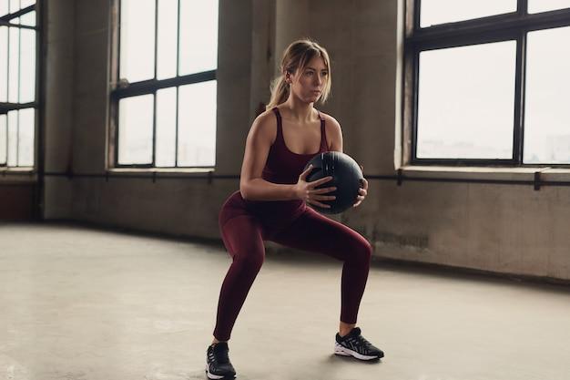 Спортсменка на корточках с мячом в тренажерном зале
