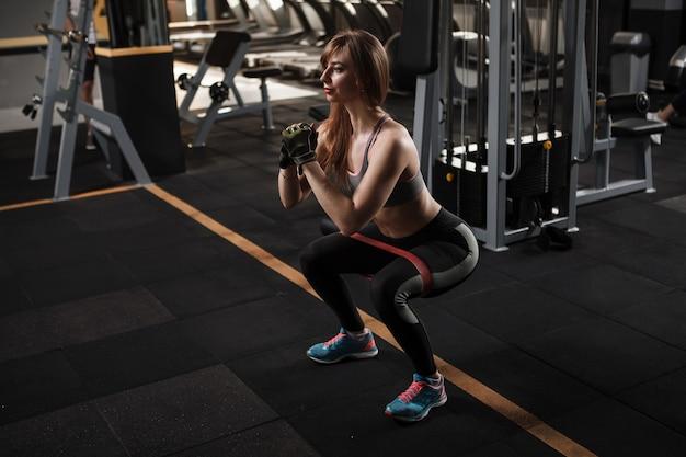 Спортсменка на корточках с эспандером в тренажерном зале