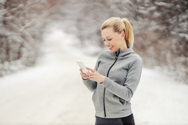 Sportswoman standing in nature at snowy winter day and texting message.