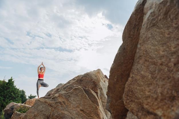 요가를 연습하는 동안 그녀의 몸을 스트레칭하는 동안 숲의 높은 바위에 서있는 운동가