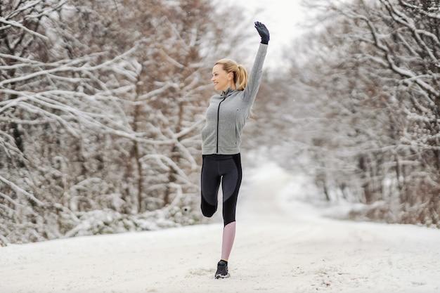 雪道の片足で立って、冬に自然の中で彼女の足を伸ばすスポーツウーマン