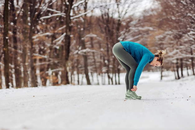 冬の自然の中で雪の上に立って、靴紐を結ぶスポーツ選手。スニーカー、冬のフィットネス、健康的な生活、自然