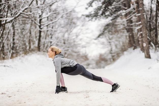Спортсменка, стоя на снежной тропе на природе зимой и делая упражнения на растяжку и разминку. здоровый образ жизни, зимний фитнес, фитнес на свежем воздухе