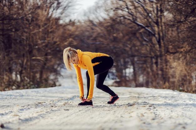 겨울에 자연의 눈 덮인 길에 서서 신발끈을 묶는 스포츠우먼. 스포츠웨어, 겨울 피트니스, 건강한 생활