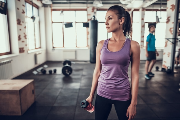 Sportswoman stands in gym with bottle of water.