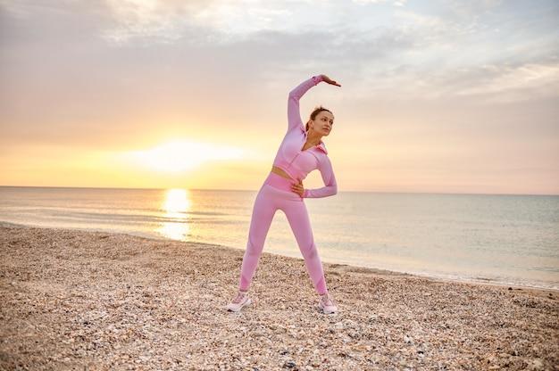 砂浜に立って左に体を伸ばしているスポーツ選手