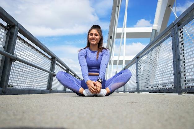 有酸素運動の前に脚を伸ばすスポーツウーマン