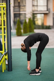 Sportswoman stretching muscles making functional training, makes a slope.