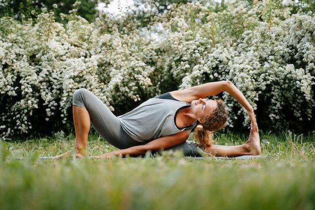 스포츠우먼 트레이너는 공원에서 다리의 힘줄과 근육을 스트레칭하는 운동을 합니다.