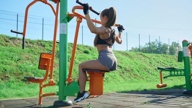 Спортсменка тренирует мышцы спины на тренажере на открытом воздухе
