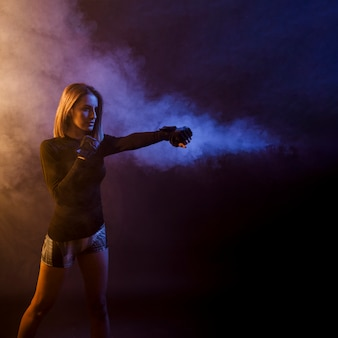 Sportswoman training box in dark studio
