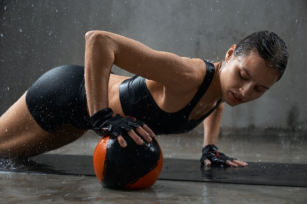 Sportswoman training on mat under rain