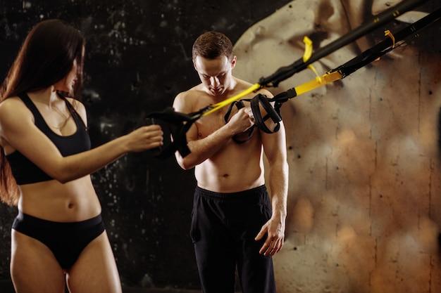 スポーツセンターのトレーナーと一緒にtrx抵抗バンドを使用してスポーツウーマンのトレーニング