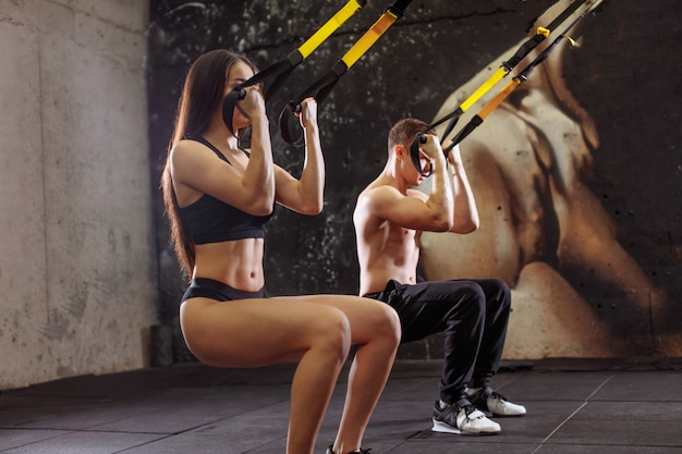 Sportswoman training with trx resistance band with trainer in sports center